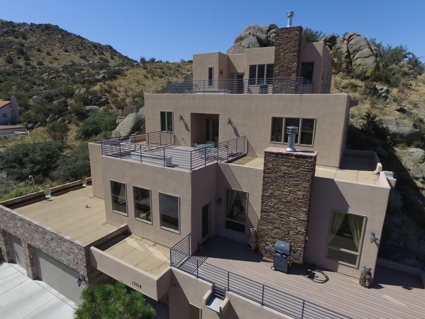Where can you find a home of this quality for only $140 a sq foot? Right here! One large bedroom with bathroom on the main floor.Beautiful custom built home with views of the city and Sandia Mountains from the many decks and balcony.Enjoy a walk in the mountains and down the quiet street.Walk up the extra wide tile stairs to the kitchen and admire the  birch cabinets,granite countertops, stainless steel appliances,and two sinks.Pella windows and doors throughout the home.Sit on the deck and enjoy the sunset as your grill outside.Beautiful wood flooring. Walk up the curved stairs to the private ''Penthouse'' master bedroom and enjoy the jetted tub, separate vanities, balcony, and large walk-in closet.All rooms are large and most provide spectacular views.Can you find the Dumb Waiter?