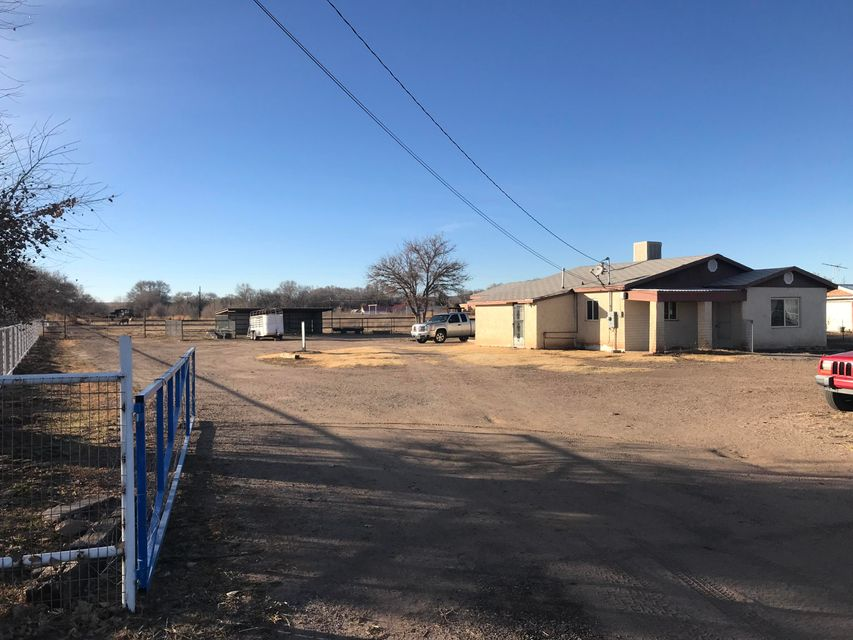 Business possibilities abound with this 2 bedroom 1 bath home with an office, on 1.34 acres. Updates include newer double pane windows, updated electric service. 125 Ft. of Highway frontage on Hwy 314 in Los Chavez, New Mexico. Additionally, the property includes a 15x30 ft. garage, a 24'x 30' covered pen area, with several attached pens. Behind the house and pens, there is a .75 acre fenced pasture. Included a 30'' road easement on the south side of the property. Gated entry, and fully fenced, this is the perfect place for a variety of possibilities. Come and see!