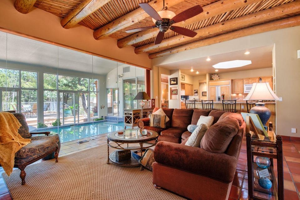 Just reduced to $740,000! Located in a cul de sac @ ABQ. Ranch Estates, a gated neighborhood, children can enjoy the freedom to play outside & just be kids..safely!!! As you enter thru the double, leaded glass wooden doors, your eyes sweep over the warm SW living room with a wood tongue & grooveceiling treatment with huge vigas a Kiva style fireplace & warm Saltillo tile floors. Your view continues east to the floor to ceiling windows framing the enclosed swimming pool & then out to those magnificent Sandia Mtn. views. This dramatic 31' pool , plus hot tub lead out to an oversized, wood deck, entertaining area & large, private rear yard w/ dramatic mountain views. Truly a WOW factor upon entry! The living room is open to the gourmet kitchen with centerisland.