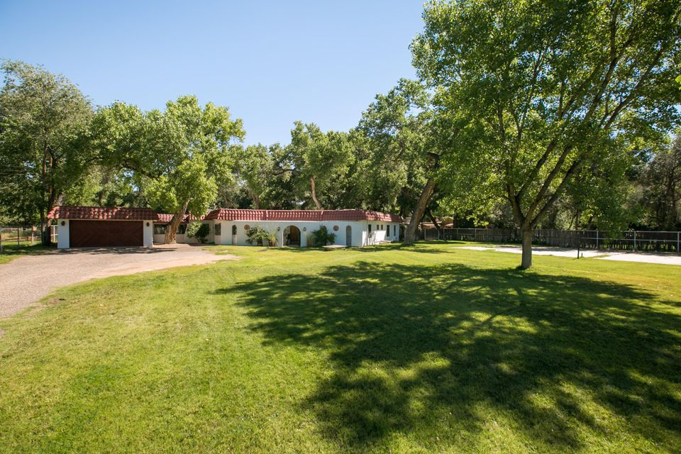 Fabulous Corrales hacienda in a desirable eastside location! Nestled under mature cottonwoods, this well maintained home offers a flexible floorplan. A separate mother in law quarters, or at one time was used by a baker to cater. Large gracious and spacious living areas. Living room features a step down, brick floors, kiva fireplace, vigas, & a gorgeous view of the lush yard. An elegant formal dining room, a kitchen that is awaiting for you to turn into your dream kitchen, large family room that boasts the outside lush grounds, a huge recreational room w/hot tub & room for a pool table! A separate gardening shed. 2 car garage. New roof w/warranty. A truly beautiful property. Access to the bosque & trail system. South end location for the great escape to city conveniences.