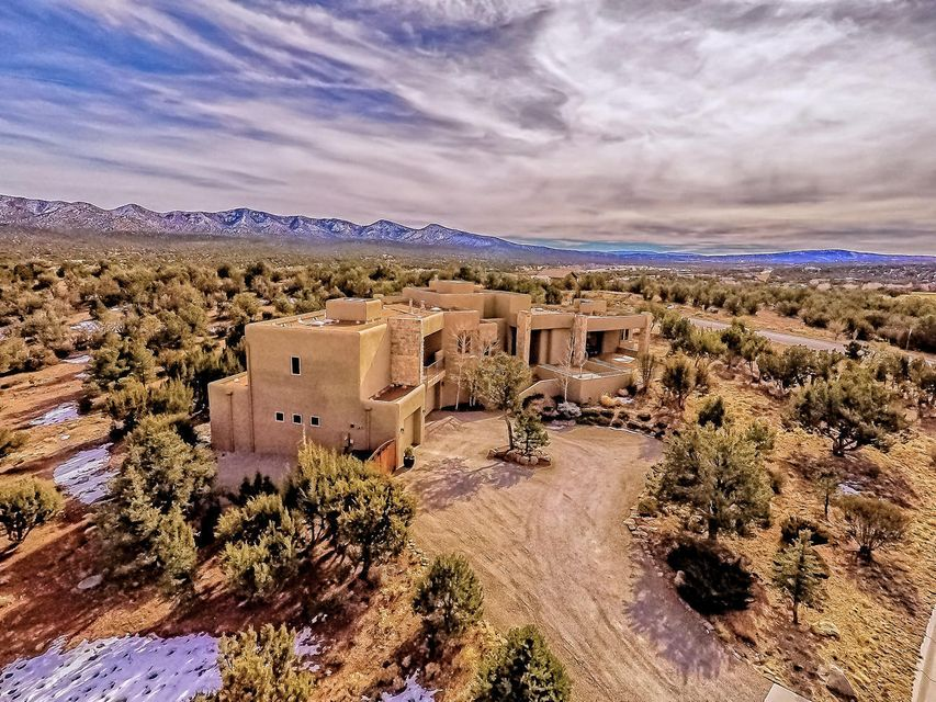 This exquisite home was designed to meet the needs of the sophisticated homeowner. Boldly embracing the architect's vision of blending chic modern w/nature's beauty, it is a high function retreat in the desirable golf course community of Paa-Ko. It offers mountain views, a quick drive to play golf or eat at The Grille and convenience to Albuquerque and Santa Fe. This home offers 3 BRs, a luxurious master suite w/exercise room, office and fantastic chef's kitchen. Ideal for entertaining inside and out. Heated and cooled 232 SF workshop, 4-car garage, lots of storage, RV parking and much more. Seller will consider TRADE or CREATIVE Financing. Priced far below replacement value. Features - Alarm system, separate wet bar with frig, built-in bookcases, cable TV, formal DR, foyer, great ro