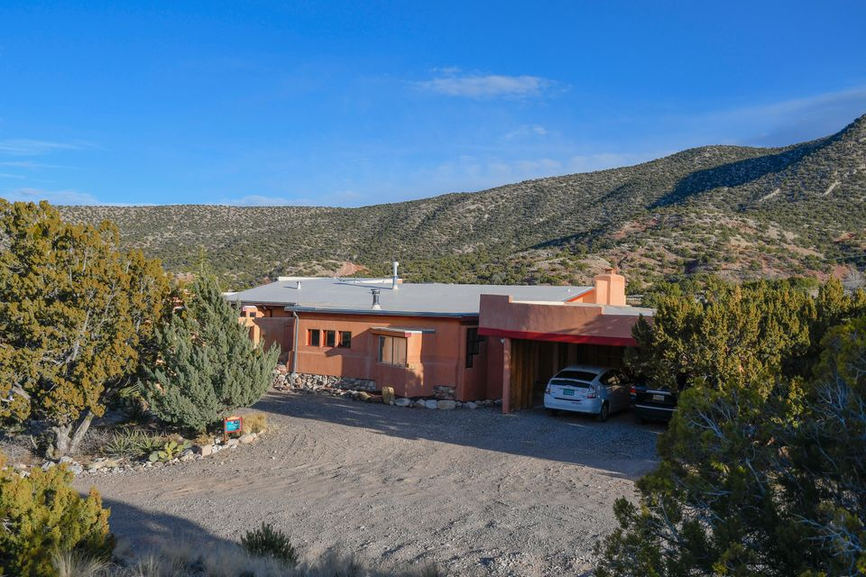 Fascinating in its uniqueness with panoramic views of the Sandias and Rio Grande Valley. Designed by award winning solar architect John O'Keefe from Maine,now owned by his architecture partner who has added to Johns vision. Bright and comfortable home, with two living spaces,one with a woodburning stove. Note the exterior porches, decks and sunroom. Cozy master bedroom with fireplace, plus a second bedroom on the main level. Third bedroom and multi purpose room on lower level offer separate living or recreational spaces. Multiple storage areas, a 2 vehicle carport and a one car garage. Passive solar orientation plus solar voltaic array serve to keep the carbon footprint to a minimum. A delightful home for those wanting big space, quiet, privacy and beautiful vistas in all directions.