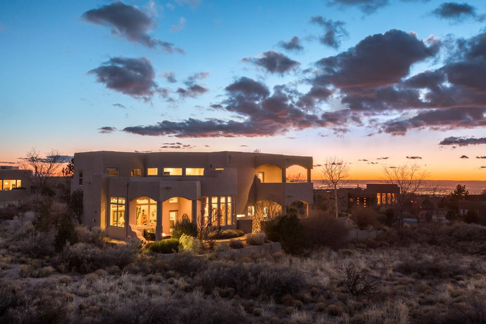 Stunning Ben Lucero custom built High Desert home! Private courtyard entry with stunning views. Large LR with a built-in entertainment center, recessed lighting and a gas fireplace. The DR is open to the LR, which is ideal for entertaining. The KT is a chef's dream! Featuring granite counters, tons of cabinet space with pull outs, double ovens, an island cook-top, and a big breakfast nook. Spacious Master Suite on the main level of the home with a spa like bath and a large walk-in closet with built-ins. Upstairs you will find spacious secondary BR's, the FR (or 6th BR). The FR offers a private balcony & built-ins. Also on the main floor you will find a study/BR.  This home features mature landscaping, four private patios/decks w/incredible, wide ranging city, sunset, and mountain views!
