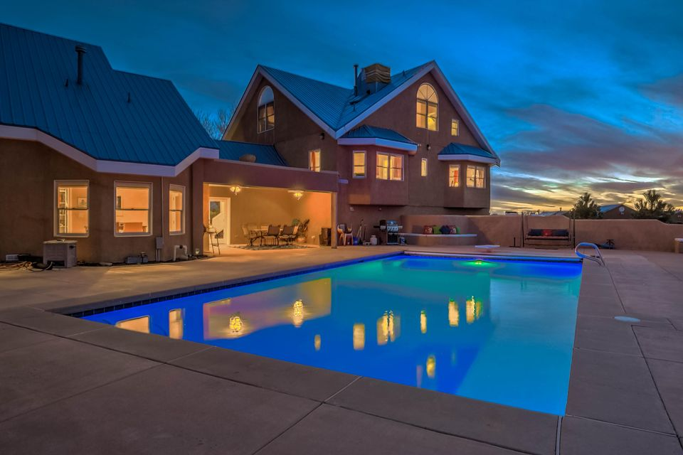 Welcome to this amazing, custom built, New Mexican style hacienda. Watch the sunset reflect off the mountains and pool as you sip a drink under your 250 sq ft covered patio.  Entertain the masses with your chef grade kitchen: Wolf stove, Sub Zero fridges, Copper farm sink and large kitchen island. Host the extended family with ease thanks to a second living space with a kitchenette.  The 4 car garage & abundant storage provide plenty of places to stash your toys. Soak in the city views off the deck in the master bedroom.  Custom details are at every turn:  hand-painted tiles, tongue and groove ceilings, window benches, walk-in closets galore, ensuites for nearly every room, and fireplaces to cozy up to with a good book. Your dream home awaits...
