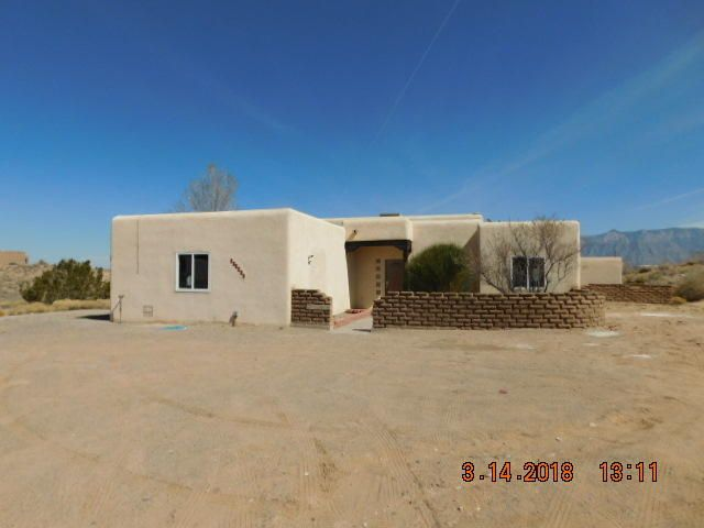 Enjoy the panoramic views of the Sandia Mountains on a large private corner lot! Lots of room for your toys and cars in the 2 car garage and large carport with a ceiling high enough for a motor home. The kids will love the little playhouse off the covered patio and the large play room inside the house.