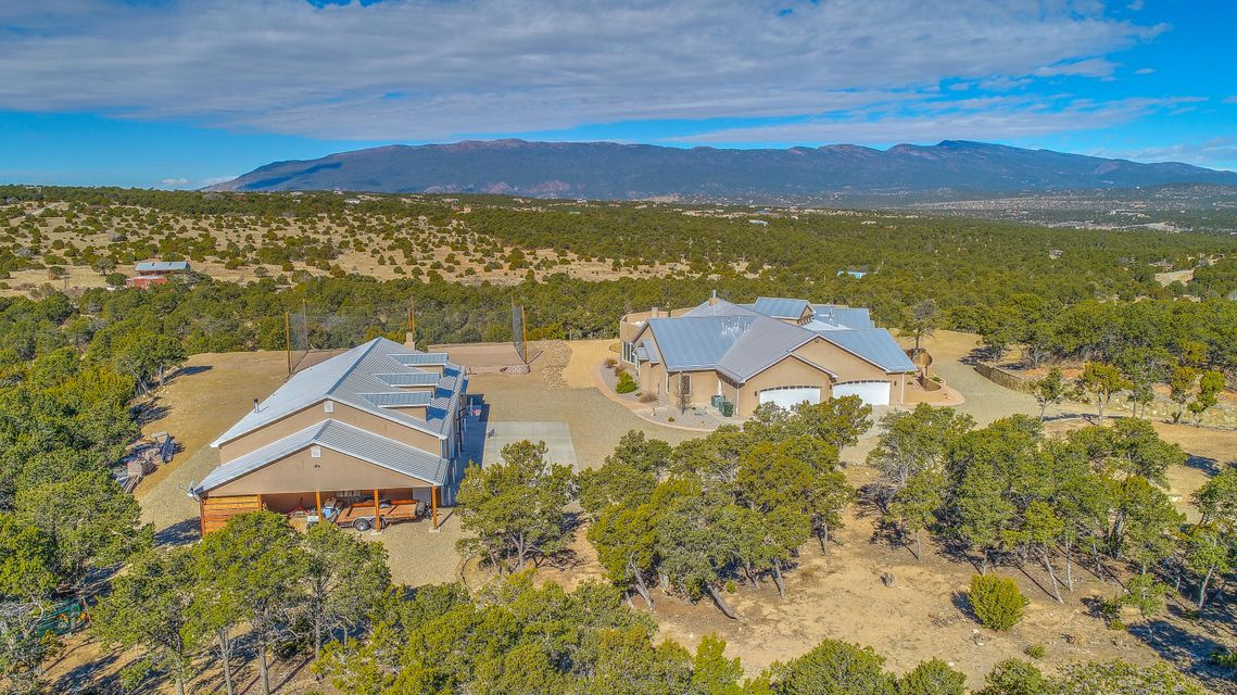 Looking for Convenient, Quiet, and Green?  Would a truly spectacular view from every window interest you? How about a casita or a huge garage for your car collection? 16 minutes to great shopping and theatres. 31 minutes to ABQ International Airport- really. This city-mountain retreat is the amazing gem you must see from a drone's perspective! Go now to the drone video link. A true Chef/Baker's Kitchen with Gourmet gas-top, oversized 'live-in' pantry room and top-of-the-Line cold food storage for superior meal-prep. Spectacular views while you cook and enjoy conversations in this modern great-room concept floorplan. Separate dining area provides for the more formal occasions or flex-use.