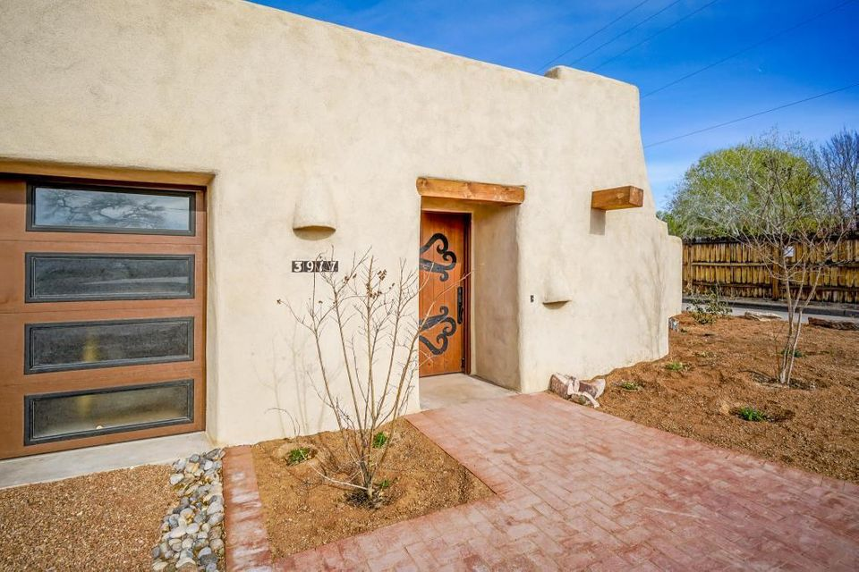 COMPLETELY RENOVATED & added to over the past two years by Adobe builder Joe Grady, custom adobe home located On dead end street that backs up the Bosque.  Original core adobe was built in 1915 but  Includes massive walls & beautiful diamond finish plaster throughout that tie into old school beam & viga ceilings. Kiva fireplace in living room. 3 exterior patio areas. Very unique floor plan. In ground gunnite hot tub w/gas fired heater. Outdoor grill & cooking area. Unique details are evident in every room. Handicap friendly, no steps, stoops or curbs, & two very large showers. Lg 2 car garage w/exposed adobe walls-extra parking area in back. Automatic bubblers for low maintenance landscape areas, security system. High end appliances & fixtures were all part of dramatic tranformation.