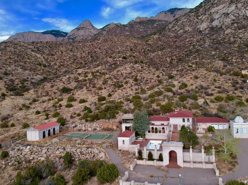You've seen it.  You have heard about it... and now it is for sale..  This is one of the most sought after properties in Albuquerque it's located in the foothills of the Sandia and sits on the edge of the National Forest with magnificent unobstructed views of the City. Sunsets are Amazing! Situated on 4 Acres with Observatory Building..  Tennis Court, Fiberglass Pool, Pool House and Tower with roughed -in bathroom could be a Guest House. (square footage not included in the 3700SF main house.  The home is being sold ''as is''. The age of the home is approximate..  Title will verify.
