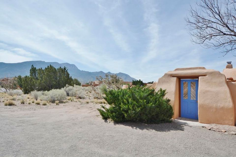 WOW!  Picturesque views of the Sandia Mountains!  HUGE private courtyard and East facing covered patio to take in the beautiful views and relax and enjoy the nature of Placitas.  Custom Tom Ashe home featuring 3BDRs PLUS a large study/den/or flex room.  Incredible views from the great room, dining room, kitchen and master suite.  Rich in character and style, this open floor plan is perfect for easy entertaining with an oversized great room featuring a wood burning Kiva fireplace, Viga ceilings, exposed adobe style walls, Saltillo tile flooring, wall of windows and French doors to the courtyard.  Dining has French doors to the covered patio at the backyard.  Master suite has a cozy Kiva fireplace, mtn views, patio access, Viga ceilings, jetted tub, dual sink vanity and two walk-in closets.