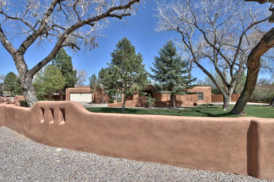 OPEN SUNDAY 6/10 1-3 pm. Beautifully updated one story Pueblo style home on .66 acre is nestled under giant cottonwood trees in Village of Los Ranchos close to Rio Grande walking trails. Southwestern detailing:beam ceilings, kiva fireplace, brick floors, double door entry & wide portal. Recent upgrades include all bathrooms,central refrig AC (plus extra unit to chill MBR way down), MBR gas fireplace, hardwood floors,plantation shutters, & security system with cameras. HUGE,high ceiling garage addition has 10' & 8' doors plus side & backyard access. Workshop, storage & lots of room for 4 vehicles.   Spacious private backyard has covered heated pool, hot tub, poolside ramada for shade. Enjoy al fresco dining on the deep porch. Plenty of room for games on the grass, garden or even a casita.