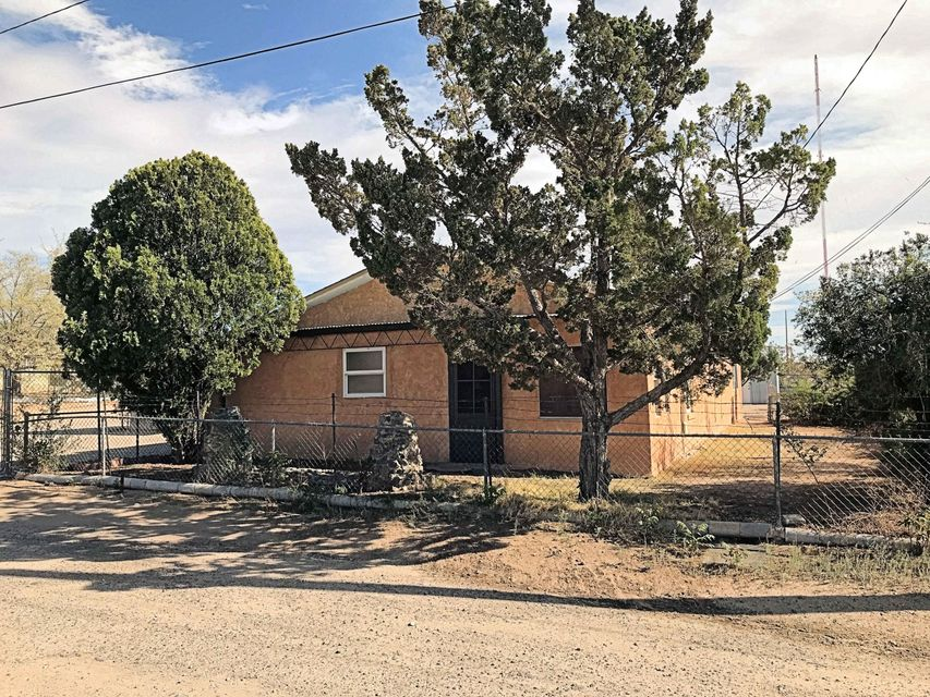 Looking for an adobe home with potential?  Here's one that is priced to sell.  This is a great fixer upper with lots of possibilities.  The home is located in a quiet neighborhood just a block off of Broadway with easy access to I-25, downtown, UNM, Nob Hill, and the Airport.  It's located on a large nearly half acre lot with a bonus 400 sf guest house.  Place a wood or gas stove in already set area with chimney and add large 300 sf room on south end of home to square footage!  Near country living in the city.  It could also be a great income property.  Come and take a look.       The property it fully fenced with a gate securing the driveway.  Plenty of room for work vehicles or even another addition.  Lots of possibilities to consider, sold as is condition.