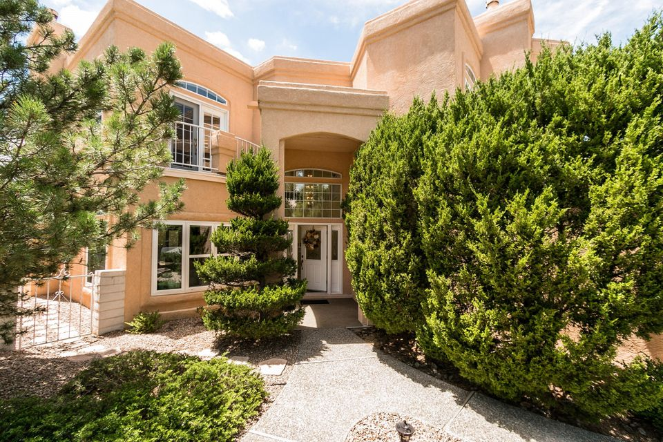 Beautiful Tanoan home on corner lot surrounded by manicured gardens! Soaring 2-story foyer leads to formal lvg rm with lg bay windows. Fmly room offers wainscoting, beautiful FP w/ upgraded mantel & views to a private garden oasis. UPGRADED kitchen w/ granite counters, island, b'fast bar, SS appls. 2 owners suites, both w/ balconies, walk-in closets & mountain views. One suite offers a cozy FP. Skylights & lg windows thru-out bathe home in natural light. 3 full baths, 1 on main level w/ walk-in shower w/ seat. 3 balconies offer 3 outdoor retreats w/ views of mtns & city lights. Great storage thru'out. REF AIR! 3-car garage w/ storage & walled bay for a workshop. 2 NEW water heaters, one fully dedicated to the main owners suite. A wonderful home in a coveted location just waiting for you!