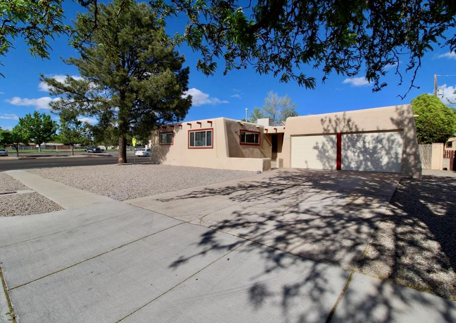 This nicely updated 3 bedroom home has a great floor plan with lots of windows, 2 living areas, and an enclosed sunroom!  It sits on a large corner lot with mature trees, has a TPO roof, granite countertops and new tile in the kitchen, updated vanities in the bathrooms, brand new garage doors and openers, and newer stucco.  Great value in the NE Heights - located directly across from Mitchell Elementary School.