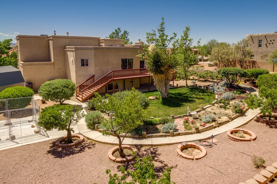 Captivating views, Bosque/trails across the street, and so many features to take in from this custom Hinkle Split level Home. Located on a corner lot  with plenty of open space, side yard access/RV Parking and plenty of extra room for all the toys + 3 car garage! Walk into an abundance of natural light with the open, Bright... living, dining and kitchen. Step out of sliding glass doors onto the Wonderful Redwood deck overlooking the expansive fully landscaped backyard. Buyers will enjoy a private Master Suite with cozy seating area! The master closet will certain satisfy!