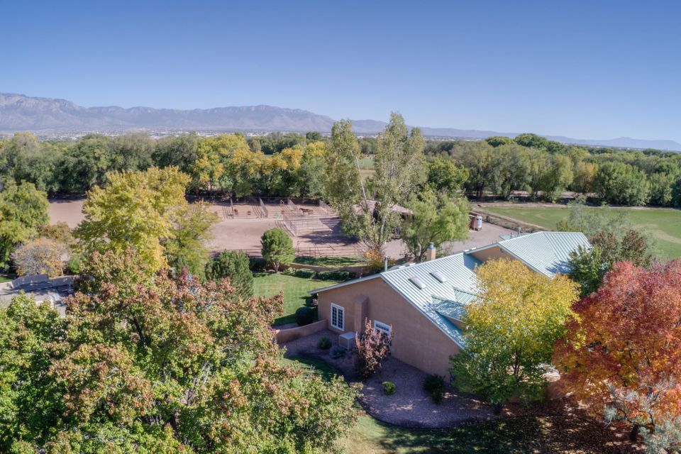 Welcome to one of Albuquerque's finest Equestrian Estates!Located on over Two Luxuriant Acres and nestled next to the Bosque for instant access for riding, bicycling or walking.You'll think you died and went to Heaven! Five Stall Barn with Attached Outdoor Runs+Four Additional Runs with a Large Arena. All areas have Automatic Water. First class Pipe Fencing for Horse Safety and Durability cover the entire property. A Special Covered Parking Area for Trailers complements the 2217 s.f. Barn. A Gorgeous Northern New Mexico home boasts Soaring Ceilings, Hardwood Floors, Architecturally Intriguing windows and skylights, French Doors, 2 Way Fireplaces and 3 Ensuite Bedrooms downstairs with 2 Bedrooms+All Purpose Room Upstairs.All this is nestled in a Green Oasis with a Lovely Outdoor Living Area