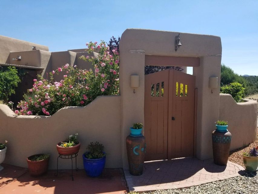 CANNOT BE SHOWN FROM 6/20 THROUGH 6/24.   Tucked away with end-of-the-road privacy and serenity, this warm, pueblo-style home offers a sun-filled, open floor plan and is surrounded by private outdoor living spaces, colorful plantings, flowering shrubs and a starburst of flowers*So many amenities! *Mountain views*Clear, sparkling night skies*Plenty of space for your pets/animals*A chef's delight kitchen w/ granite counters and cherry cabinets*Beamed ceilings*Spacious formal dining plus breakfast nook*Great Room living highlighted by the Kiva fireplace* Over the past   few years the carpet, roof, hot water heater, boiler, water softener, dishwasher, washer and dryer have been replaced*All yours in an enclave of fine homes!  Beauty that must be experienced