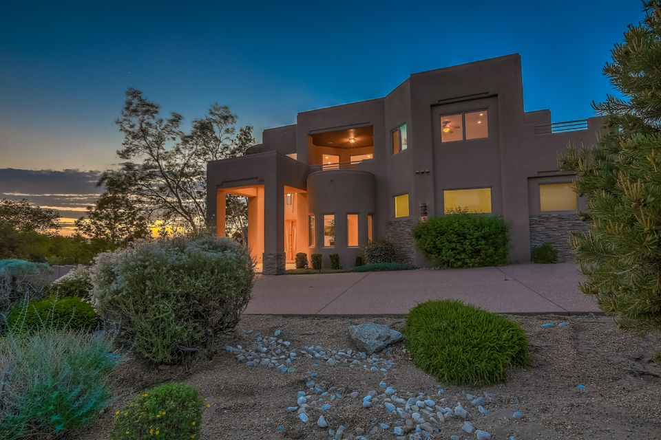 Enter through the custom carved-wooden door to a thoughtfully-designed home capturing the majestic Sandias and twinkling city lights from every window and deck. Created for entertaining with open spaces, high ceilings for volume.Large bar area with oversized wine frig Cook's kitchen with 5-burner gas stove, Sub-zero, prep sink & two dishwashers. Retire to the sound-proof media room with blackout shades. Abundance of space  in large master with double closets, steam shower and jetted tub. Gracious upstairs living area with gas fireplace adjoins 2 additional bedrooms. There is an additional en-suite bedroom as well as a separate en-suite bedroom with separate entrance.Enjoy the outdoors and views from private patio, grill and bar with granite. ''Zero closing cost'' loan potential. Mortgage