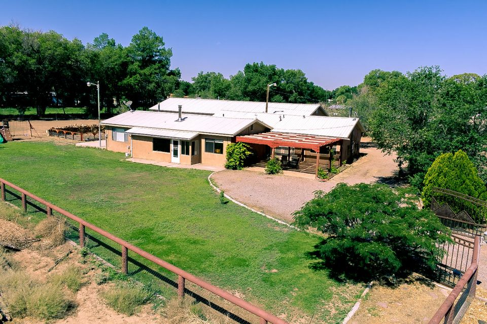 Two homes for the price of one in the heart of Los Ranchos De Albuquerque! Come see this lovely property situated one acre that can be subdivided in two if so desired, and have the choice of a sold rental income or keep one home and sell the other for instant equity if you choose. The possibilities and options are endless. Come home to a country lifestyle in the center of Albuquerque with a total of 4 bedrooms, 5 bathrooms, an oversized 3-car garage, and close to 4,000 sq. feet of living space between the main house and the casita/office/workshop. If you are looking for an in-laws quarters close but still separate on the same irrigated lot this is the ideal location.  Bring your horses, have ease of access to Paseo Del Norte, and all the wonderful amenities that the North Valley affords.