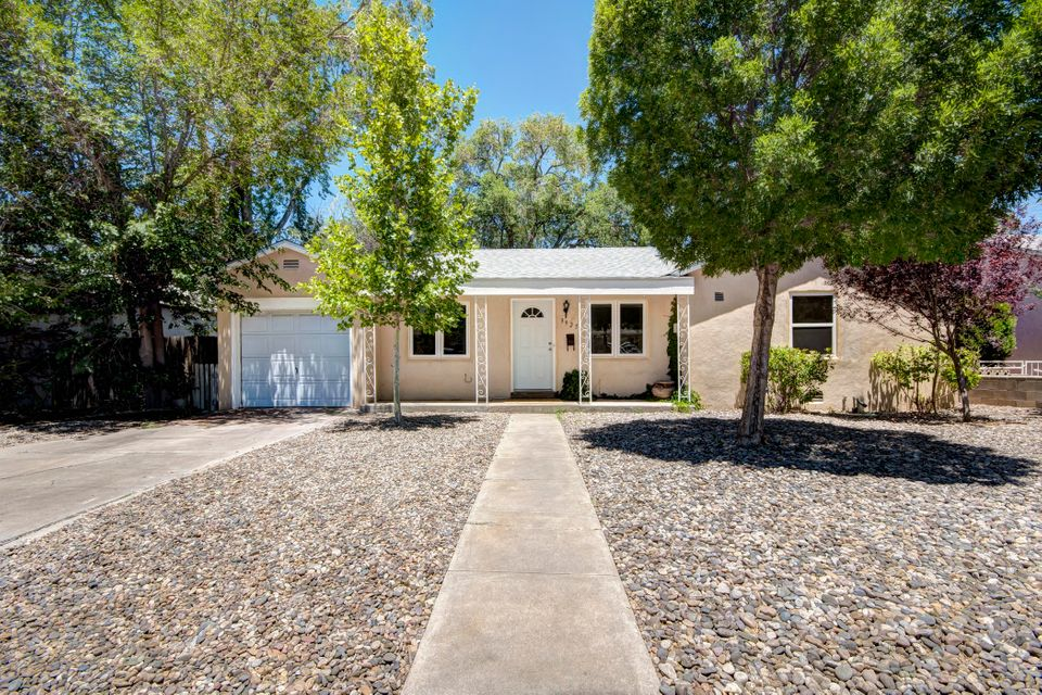 Beautifully updated home in desirable and established UNM neighborhood! Original hardwood floors welcome you into this light-filled 4 bedroom/three bath house. Fantastic kitchen just updated with white cabinets, beautiful counters, new refrigerator & stove plus a cute breakfast nook! Arched doorways in main rooms, cove ceilings, and marble hex tile add vintage design and charm. 4th bedroom makes a great second living area. New roof in 2017 with transferable warranty, refrigerated air, abundant storage throughout & new windows! Single car garage. Large yard with deck for those beautiful evenings. Monte Vista & Jefferson school district! Short walk to Humble Coffee, Hidden & Twin Parks. *Open house Sun 2-4*