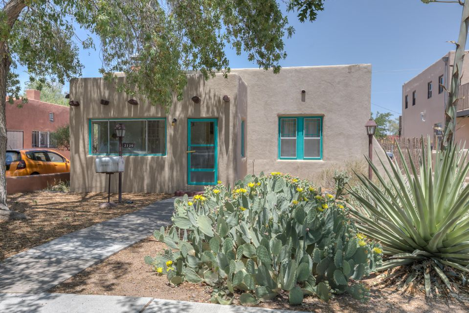 Classic 1920's era adobe featuring authentic detail combined with modern updates and amenities.  Great location in the Silver Hill neighborhood just a few minutes walk to UNM.  Features include a large living room with china cabinets; unique arched French doors lead to dining room w/horizontal prairie windows; arched entrance to kitchen w/b'fast bar & pantry. Also: front-of-house wood beamed ceilings, recessed, hardwood throughout, 2 deep bedroom closets & hall closets; heat/cool combo unit! Heated 560 sqft lower level has furnace & H2O Heater; tiled 3/4 bath & office/media room, extra storage & private exterior walk-out.  Detached garage/storage.  Recently installed 2.73 KW solar system provides power for nearly all electric usage. Detailed floorplan available