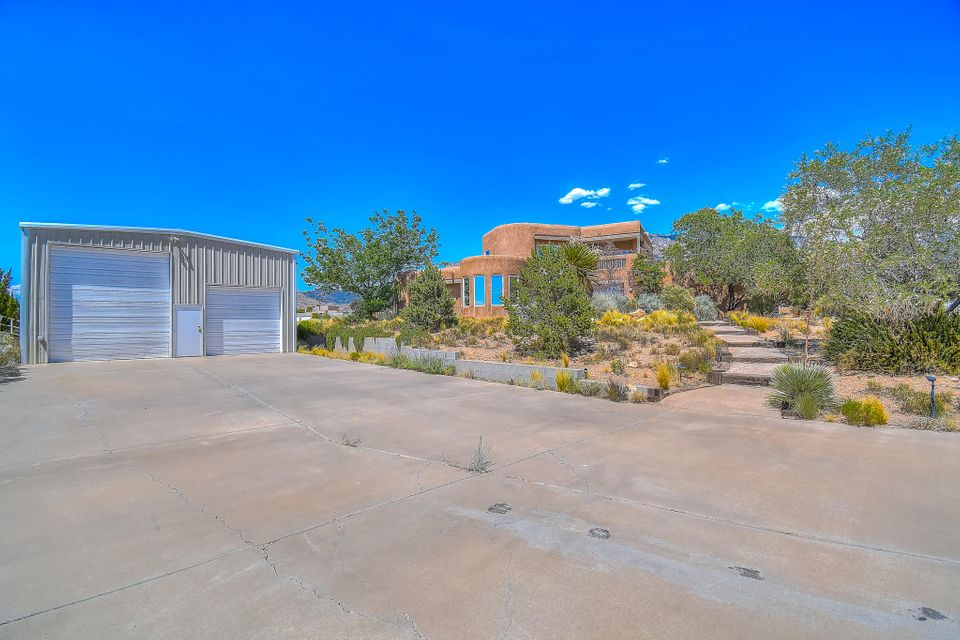 **Open Saturday, June 16th from 11am - 2pm** This phenomenal North Albuquerque Acres dream home is masterfully designed to face dramatic views of the colorful Sandia Mountains. Yes, that certainly is a heated / refrigerated air cooled 1,500 square foot workshop steps from the front door - WOW!!! Cross the threshold and you'll be electrified with excitement taking in the soaring ceilings, numerous windows drenching the home in cheerful natural light, views from every direction and outstanding open floor plan with spacious rooms throughout. The private master suite takes up the second floor and includes a living area, enormous bathroom & walk-in-closet, and private patio surrendering unbelievable views of Albuquerque's city lights. Purely dynamite!