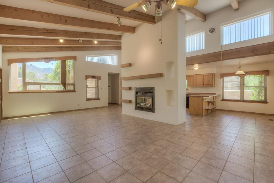 1-Story east of Tramway on a lovely street in Sandia Heights beneath the foothills spacious open floorplan w/vaulted beamed ceilings, living/dining room & kitchen separated by elegant 2-way fireplace, Owners suite with double sinks & door to backyard patio, large 2nd and 3rd bedrooms with full bath in between updated Champion windows & doors, clerestory windows, wood blinds, newer foam roof, awesome outdoor living spaces with stuccoes walls, lovely perennial flowers & bushes w/soaker hoses that keep this oasis a bird's haven! Lovely backyard w/covered patio & additional yard beyond the west wall! The east facing courtyard is finished with flagstone, 2 gates and some incredible mountain views, the perfect place to enjoy those ever-changing majestic mountain views! It's an ABQ Dream Home!