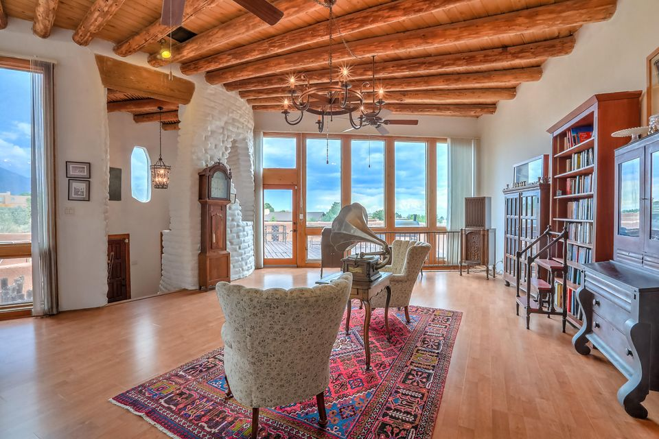 Very nice Rare and Unique Adobe Offering in Sandia Heights. Great location, Great views, Great setting! Enjoy 2 living areas in this 5 bedroom/3 bath Adobe home! Wonderful SW Accents/character throughout the home. Great main floor living area with vigas, high ceilings, lots of light/windows, Huge Kiva fireplace and dining area. Kitchen has been updated w/ newer cabinets, granite counter tops and stainless steel appliances. Living area also has a walkout to a huge view deck. Nice master suite w/ updated 3/4 bath, fireplace and views. Lower level has 2nd living area, wet bar w/ small cook top, two additional bedrooms & 3/4 bath. Walled front patio has a hot tub with great views. Home has updated heating/refrigerated air cooling and  newer advanced treatment septic system. Don't miss this one