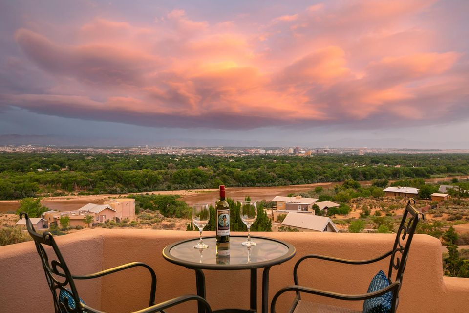 Perched on the bluff with Sweeping views of the Rio Grande,Bosque, Sandia Mountains and City Lights.This is a rare opportunity to live in one of the most special locations in all of Albuquerque.Custom architect designed w/a taste of Taos farm house & contemporary SW.Gorgeous vaulted latilla ceilings,art ledges & walls of windows to enjoy the amazing views. 3 frplcs, 2 living areas both with views,Master on main level with fireplace, view deck, and luxury bath with double sinks, separate shower & tub & HUGE walk-in closet.There are even views from the tub and shower!2 BR and office or kid den or workout rm on lower level sep from master. Front courtyard w/heated pool.Detached over-sized 2 car garage..59 AC lot in the County, so lower taxes! This is a gem - your chance to own a special jewel