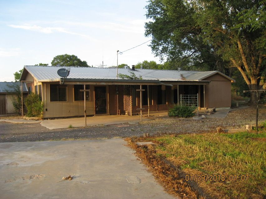This property is located on over 6 total acres of agricultural land with irrigation and pre-1907 water rights!(Buyer should confirm with SEO) Several outbuildings with several pipe fenced corrals. The home has 3 bedrooms, 3 bathrooms, metal roof and fairly new furnace. Two of the bedrooms have their own full baths.  Large front enclosed patio room (15.5'x9.5', 147sf) not included in square footage. Come bring your horses and other livestock and enjoy the quiet setting this property offers back off Camino De Los Chavez and adjacent the irrigation ditch.  This property has great potential.