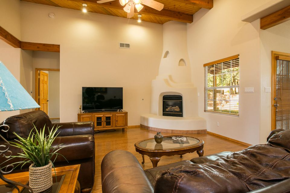 Peace and tranquility close to the heartbeat of the city!  Bio-park, Old town, Sawmill, and downtown are all just a walk, stroll or bike ride away. For an evening at home relax under the covered portal soaking up the beauty of your landscaping and the greenbelt behind you! In the winter enjoy the dramatic great room with wood floors, contemporary kiva fireplace and soaring ceilings. Updates include granite countertops, new dark stainless steel appliances, wine fridge, seamless gutters, and water softener.  MSTR bedroom has wood look tile flooring, romantic kiva fireplace and generous en-suite bath.  Additional bedrooms feature wood floors and plenty of natural light. You must see this private and pristine gem to believe it!