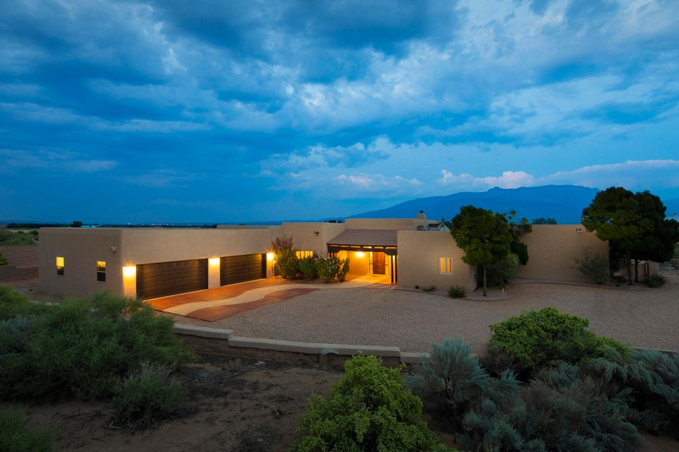 Stunning Southwest style resort like home located in Corrales on a large 1.17 acres with majestic mountain views! Home features 4,289sf with 4 bedrooms, 3 bathrooms, 2 living areas, a 4-car garage and private pool! Travertine flooring in wet areas! Gorgeous living area with a raised wood beam tongue & groove ceiling & a custom gas fireplace w/ a natural stone surround. High-end kitchen w/ upgraded cabs, granite countertops, built-in double oven, gas cooktop, backsplash, high bar w/ seating area and a breakfast nook. Master suite w/ a kiva fireplace, outside access & spa- like bath. Bath hosts dual sinks w/ custom vanity, a deep garden tub, walk-in shower & closet! Private Oasis outside w/ a stunning pool & hotub, putting green, basketball court and racquetball court! Zoned for horses!