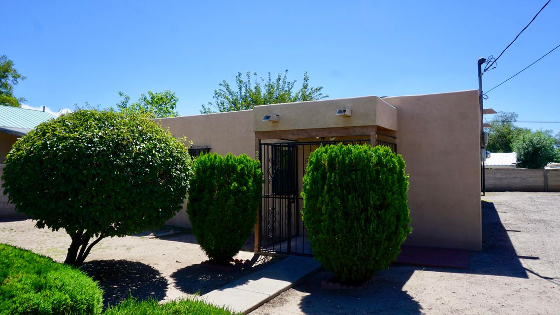 Come and see this quaint home just minutes from downtown, UNM, and freeway access! Large living and formal dining areas, nice kitchen with eat in option and newer double sink, gas range and vent hood. New water heater and newer stucco as well. Great size bedrooms, laundry area. Home is complete with double pane windows with rod-iron. The yard is walled with rod iron and has a private gated access for your vehicles to complete this wonderful property, that you would not want miss out on!