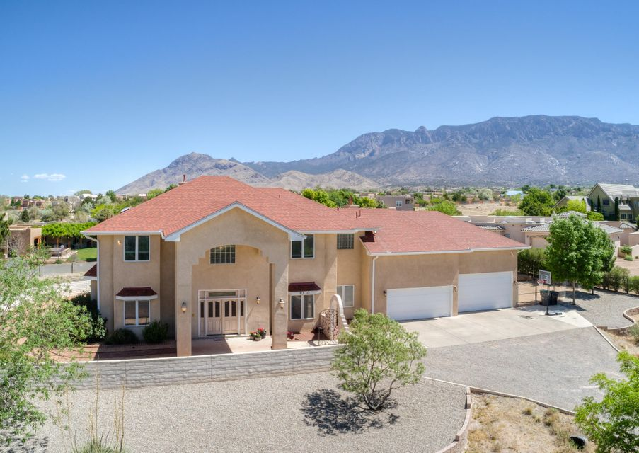 PRICED TO SELL!! This stunning custom 4350 sqft home nestled on .89 acres is an unbelievable deal in one of ABQ's most sought out areas! This large 5+ bedroom home has plenty of space for everyone including private in-law quarters. The beautiful & spacious kitchen is a chef's dream that features high end appliances & granite countertops. The 5 over-sized bedrooms all have their own attached bathrooms & generous walk in closets. The large owners suite is truly special w/ a gas log fireplace, sitting area, & breathtaking views off the private balcony. The huge over-sized 4-car garage is every mans dream garage w/ an RV door, workbench & tons of storage. Extras include a brand new roof w/ warranty, radiant floor heat, central vac, beautifully landscaped backyard w/ dog run & MORE!! MUST SEE!!