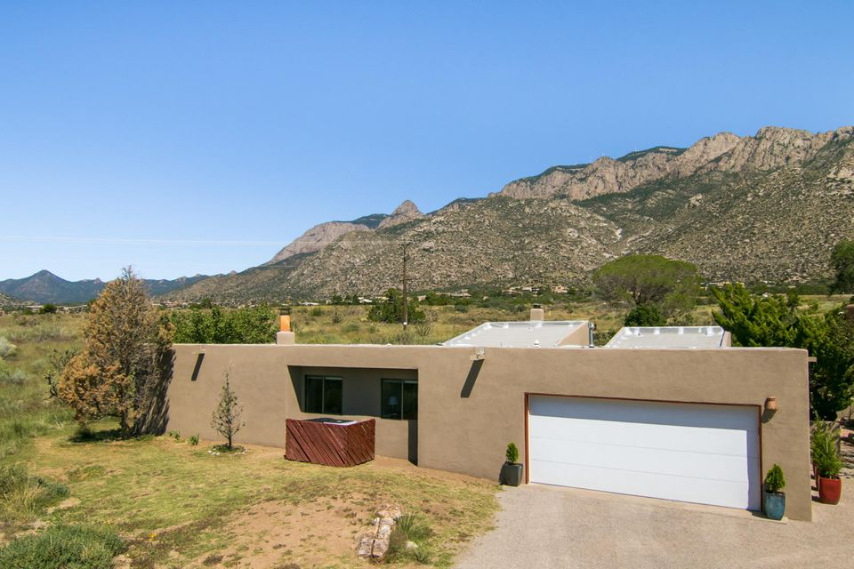 Great single level home on a large .84 acre lot in Sandia Heights. This home features a courtyard entry with stunning views of the Sandia Mountains. Upon entry you are greeted by the light & bright Living Room with east facing windows to show off the Mountain Views. Just off the Living Room you will find the Dining Room with brick flooring. Spacious Family Room with stunning Views as well as a fireplace, wet bar, & an updated 1/2 bath. The updated kitchen offers granite counters & stainless appliances. The Master Suite offers an updated bath with dual shower heads, and a large dressing room/closet. The backyard offers both covered & open patio space for taking in the unobstructed Sandia Peak views. Great location near the Open Space Preserve, Hiking/Biking Trails, and much more!