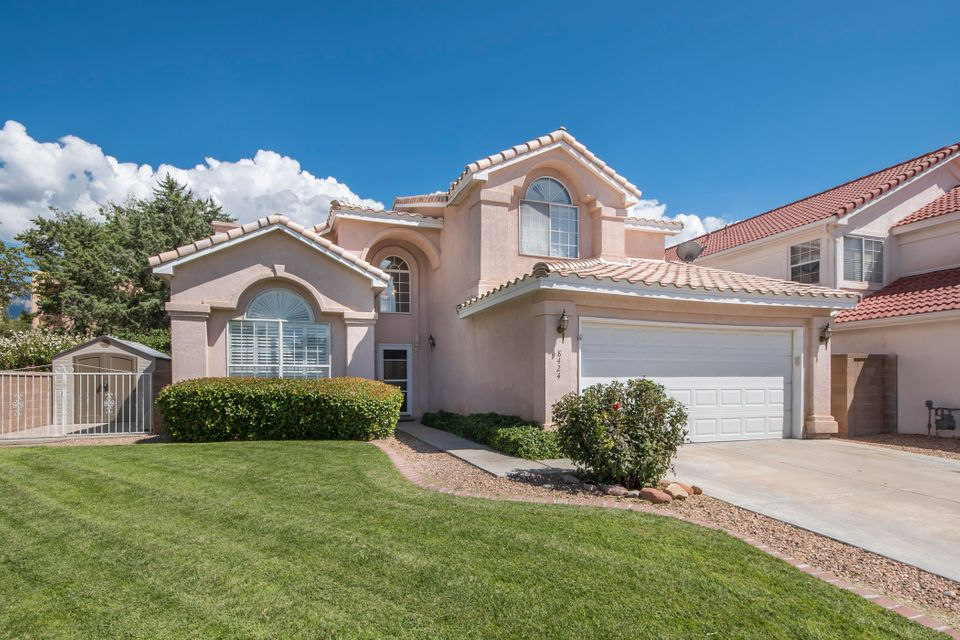 This versatile family home accommodates the extended family or the executive who entertains. Special features include oak hardwood and tile floors, plantation shutters, surround sound and newer heating/refrigeration units, roof and water heater. The chef's kitchen pleases the eye with stainless appliances, quartz countertops,  glass tile backsplashes and a charming breakfast area. The flowing floorplan  also boasts two living areas, a formal dining area and an extra bedroom with half bath downstairs. Upstairs you'll find the Master suite plus two Jack and Jill bedrooms with full bath.  Outside an inviting terraced grassy backyard  with a covered entertainment  area awaits you. This beautiful home is within walking distance to La Cueva High , Dennis Chavez Elementary and Albuquerque Academy