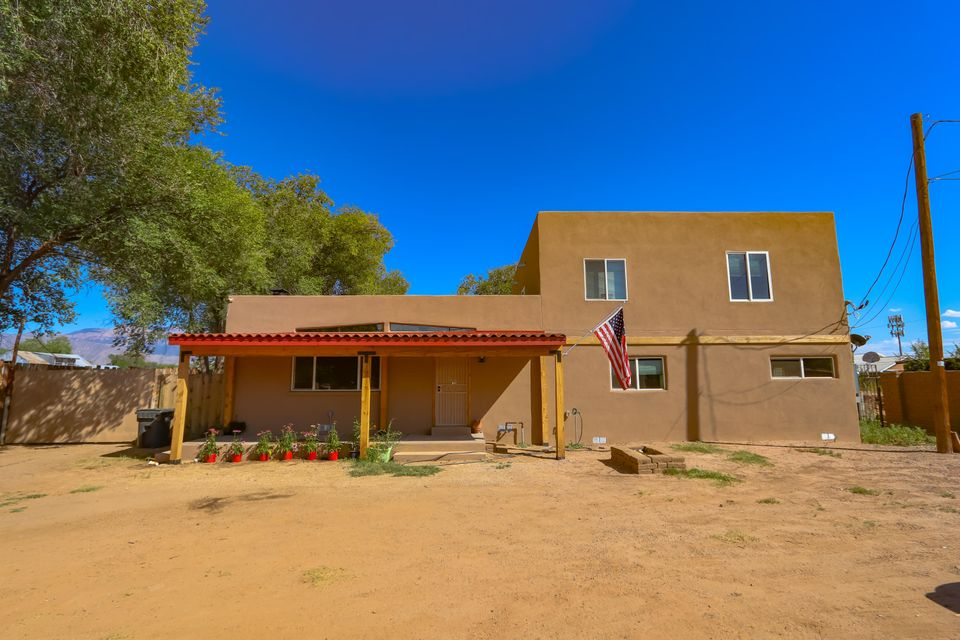 VIEWS! VIEWS! Home on 1 acre lot w/ adobe wall w/ rolling gate on 2nd St, over 3000 sqft, 4/3/4 concrete block construction, well insulated walls, TPO roof, 28x40 garage (2 doors w/remotes), attached RV barn, sheds, horse stalls & tack room, joins MRGCD ditch (water avail w/ headgate). Living area is 27x27 & features operable skylights, natural wood floors & fireplace w/ heat vents. Kitchen & dining areas (28x15 total) are open w/ bar between. Kitchen boasts a 6 burner red gas cooktop, a red antique farmhouse kitchen sink & brick floors w/ radiant heat.  Master suite (approx 27x29) is upstairs w/ a balcony overlooking the courtyard & hot tub. Bath/closet area is 10x29.  Split level heating w/ separate units for each floor. Versatile property w/ many potential uses! Antique cars? Horses?