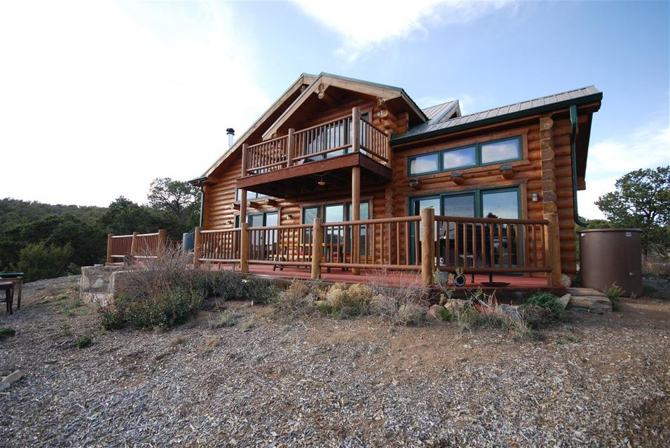 Absolutely pristine location feels like a thousand acres. This custom log home was lovingly designed and built to take advantage of solar orientation and views. Custom square logs were laid in 4 foot sections and pressed. Wrapped with decks top and bottom for outdoor living.  Cathedral ceiling in living room with walls of glass, efficient wood stove.  Stainless steel kitchen appliances, gas range, pantry.  Dining room and kitchen nook.  Master upstairs with deck, custom bathroom with tiled soak tub and double shower.  Loft can be study or extra bedroom. Guest bedroom and bath with clay walls downstairs.  Greenhouse is 16X28 and has an Endless Pool 4 deepX8X15. Barn has climbing gym, heat and cooling 24X12. Storage shed 12X12 and another tool shed 10X12. See MORE