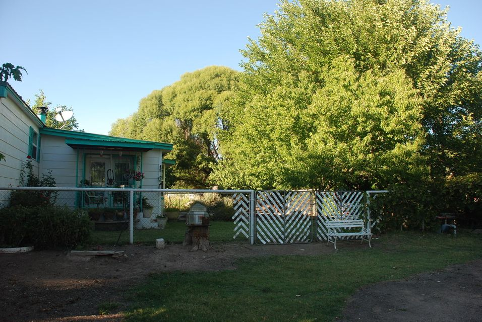 Lots of Value Here !! Three Bedroom Home For the Family with Two Living Areas. One Acre of Irrigated Valley Land with Nice Yard Garden Area and Fruit Trees,Workshop with 220 for Dad and Animal pens for Livestock.  Can sell on More than Three Acres with two additional mobile homes. Call Listing Agent for Complete Details.