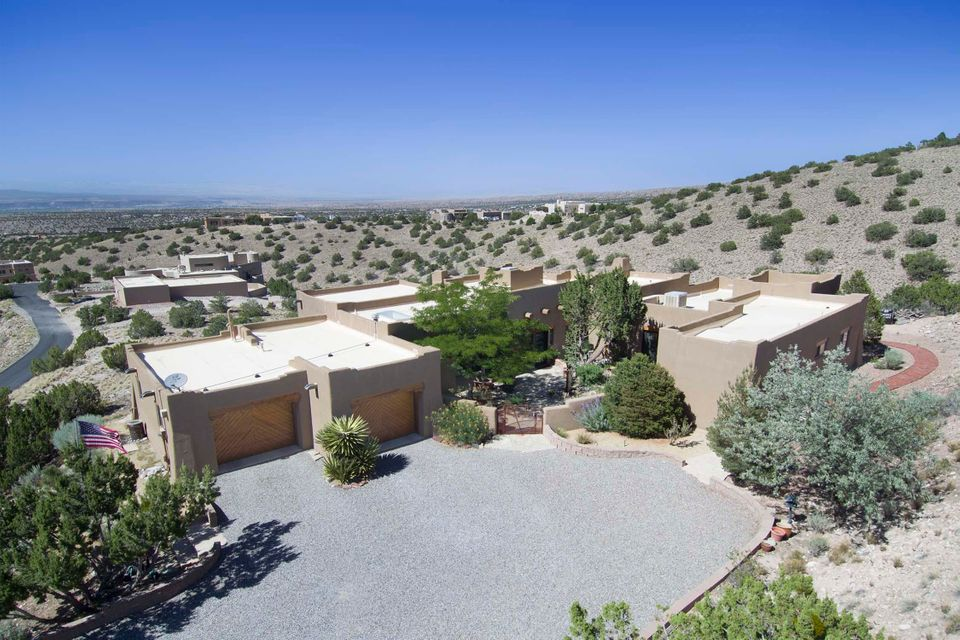 Amazing 2.74 acre property with sweeping unobstructed views of the Jemez Mountain Range.  Meticulously maintained! No pets or smokers ever. Wonderful updates in the Kitchen and both full Bathrooms. Santa Fe-style floorplan features brick, saltillo and ceramic tile flooring, wood vigas, rough sawn pine plank ceilings, wooden lintels over the windows, and 3 kiva style fireplaces. The heart of the home showcases high, wood viga ceilings in the sunken Living Room with a wall of windows. The stunning Kitchen opens to the Dining Room with another wall of windows that capture the expansive mountain and mesa views. The private front courtyard extends the living space outdoors. 4 generous sized Bedrooms. Oversized garage offers extra storage space.  See feature sheet for all of the improvements.