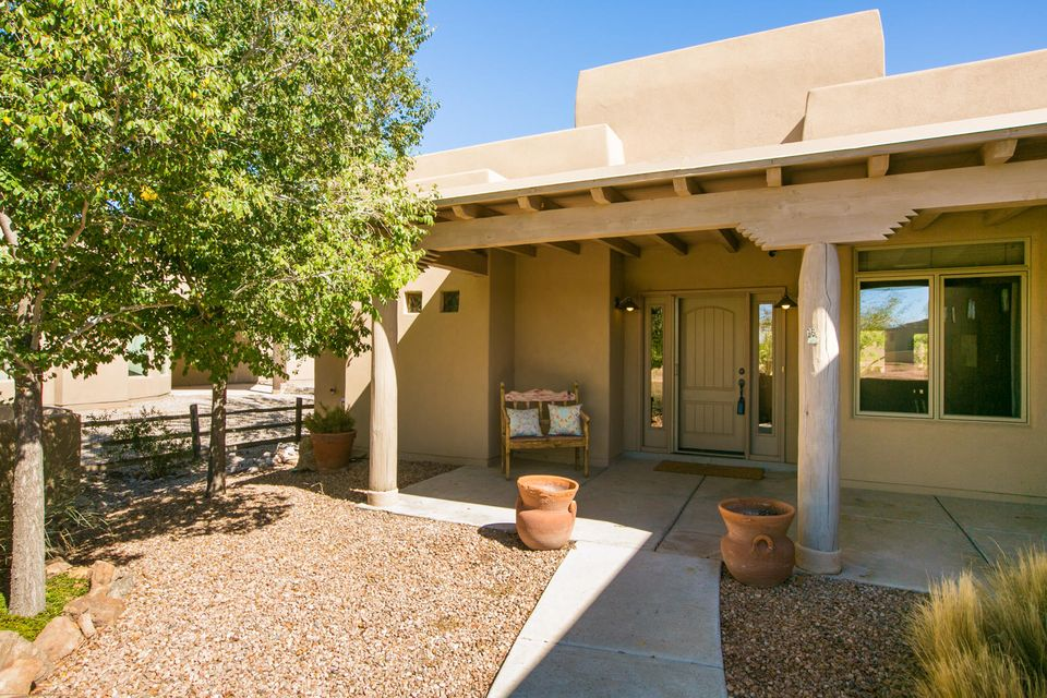 This beautifully appointed single story Pueblo Style home is located in a private gated community directly adjacent to the Rio Grande River Valley. Enjoy the beauty of the natural setting in the bosque from this charming home. Upon entering, you will be greeted by a private courtyard with custom gates. This home offers an open concept floorplan with lots of natural light, and high end finishes selected by an interior designer. Many will appreciate the attached and finished oversized 3 car garage with a separate shop, artist studio, or home office also heated with nearly 300 sq ft.  This flexible floorplan offers a beautifully appointed master suite with a custom Kiva Fireplace, a large and inviting great room, a kitchen fitted in granite and stainless steel & beautiful outdoor space!