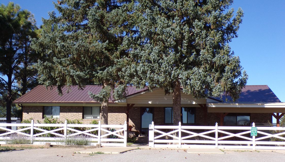This Moriarty, New Mexico horse property has it all featuring a 4-stall insulated barn with a roll-up door, 150'x300' ropin' arena currently planted in winter wheat, catch pens off the arena and a multitude of  other pens, many frost free hydrants, 60'x40' shop with power, heat, air conditioning, mezzanine storage, and office area. Not to be missed is the large equipment storage area with a concrete loading dock. This is a lovely ranch style home with 4 bedrooms, 3 bathrooms, stunning kitchen, large great room with a wet bar, heated sun room and hot tub. This home is made for entertaining especially after a fun day in the ropin' arena. The backyard is beautifully landscaped with lush turf and mature trees.  The serious horseman will appreciate the many fine details this property has