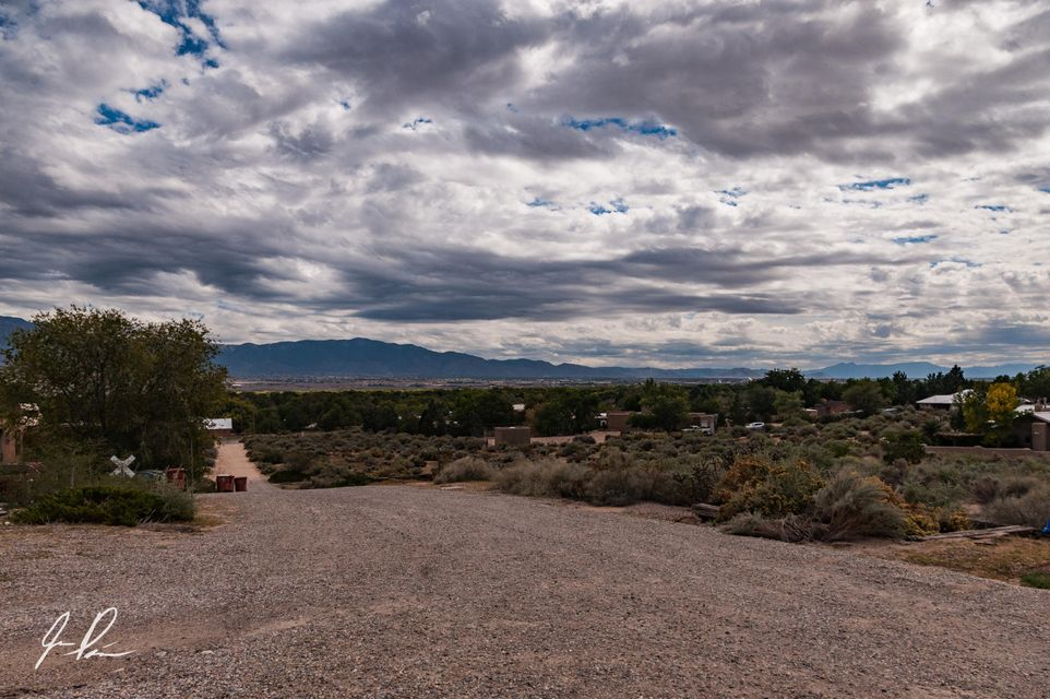 Corrales living at its best. Amazing views. Adorable 2 story townhome that sit onto of Sandia View Rd. New TPO roof installed December 2017 with a 5 year workmanship warranty. This home has vaulted ceilings with wood beams. Cozy kitchen that opens up to the spacious great room that features a Kiva fireplace. Powder room conveniently located downstairs. Full bathroom upstairs with 2 bedrooms. Master bedroom has a balcony that has views for miles. Single car garage. Backyard is fenced and private. This home is located in a townhome community that has a community well and septic
