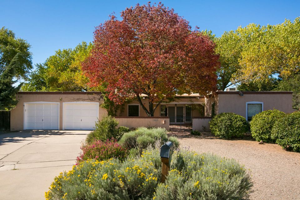 Charming single story traditional Territorial style home is located in Thomas Village, in the heart of the North Valley.  Located in a cul-de-sac close to the walking and biking trails of the bosque trail system.  This home features traditional New Mexican detailing including beamed ceilings, charming Mexican Talavera tile in the kitchen and bathrooms, brick floors throughout and two wood burning kiva fireplaces. Additionally, this home includes two master suites and a screened in porch with brick flooring and tongue and groove beamed ceilings.  Outside your own private oasis awaits, with lush landscaping, private pool, tons of shade and covered porticos. This great home offers an opportunity to enjoy the beauty of classic New Mexican architecture in a wonderful neighborhood setting.