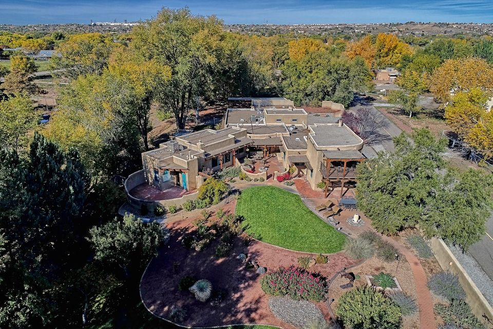 Gorgeous Taos-style adobe hacienda filled w/ light & character featuring expansive mountain views  in a lush, park-like setting. Two luxurious master suites sit in opposite private wings. Updates include 3 refrigerated air combo units, richly-textured walnut & refinished brick floors. Character abounds with viga & latilla ceilings, 4 kiva fireplaces, custom stained glass & hand-crafted chandeliers. Spacious gourmet kitchen boasts granite counter tops, 8-burner SS Jennair stoves, large pantry, 14-foot ceilings & farm sink. Huge RV carport accommodates 40' vehicle w/ convenient  220-power. 3-car finished garage has huge storeroom & room for workshop. Lush backyard is bursting w/ rose gardens & fruit trees, including cherry, apple, pear, peach & plum. Corrales country living at its finest!