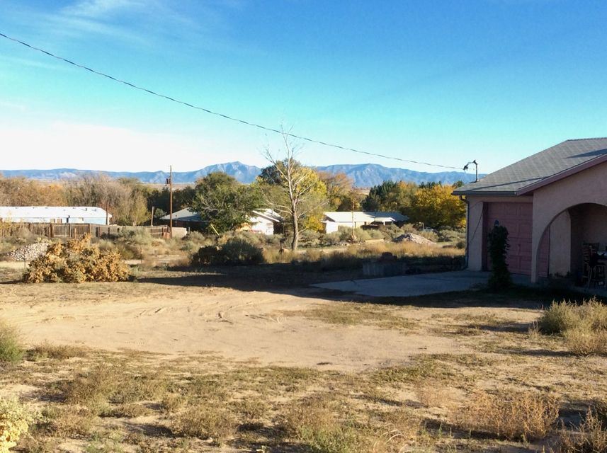 3/4 of an acre under bright stars. Sunrises, moonrises, Bosque and mountain views are all part of the beauty of this property. 2x6 construction to keep utilities reasonable, security bars, cozy floorplan. Home needs work but has so much potential!