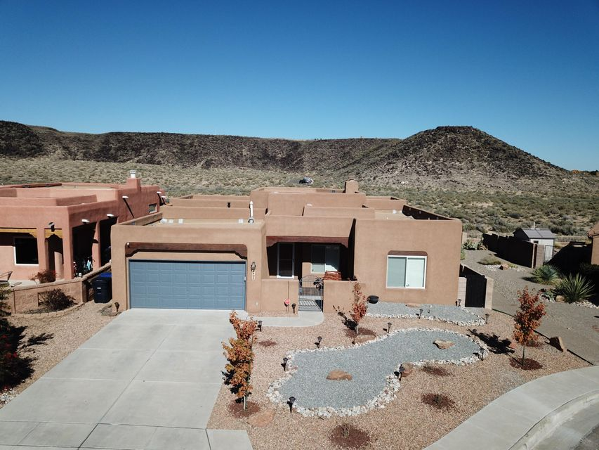 Don't miss your opportunity to call this gem, nestled in the Petroglyph Shadow Community, your home.  This custom home won't disappoint with the spectacular views of the Petroglyphs and the Sandia Mountains.  With its well designed floor plan, it boasts 4 bedrooms, 2 bathrooms, and open floor plan perfect for entertaining.  The home backs up to the open space at the foot of the Petroglyph National Monument.  Custom wood treatments throughout, tank less water heater, and efficiency heating and cooling systems.  Lots of upgrades on an already gorgeous home.  New granite counter tops in the kitchen, newly renovated bathrooms, and new custom patio cover and extended patio.    Schedule your showing today, this home won't last long.
