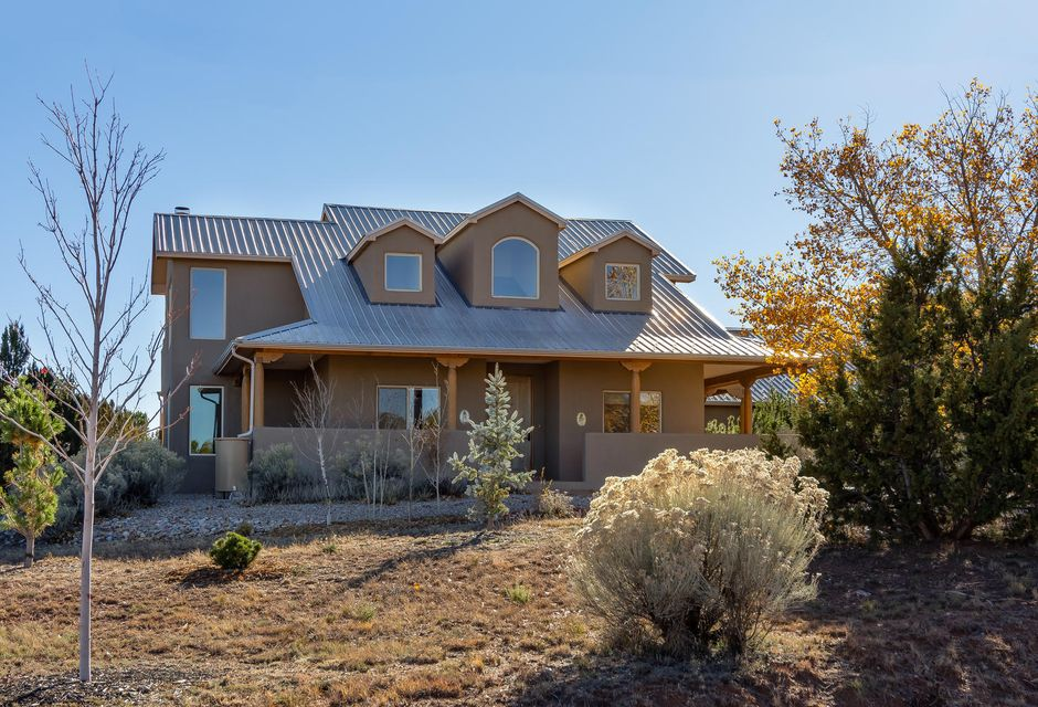 Awaken each day in spacious, sun-filled rooms to the sounds and sights of Nature in this beautifully loved and meticulously maintained, custom, Northern New Mexico-style home*Rocking-chair ready wrap-around porch*Raised ceilings*Open floor plan*Kiva FP*Mountain Views!*Private owners suite including loft and star-gazing deck*Newer stucco, Breezaire cooler, gutters and rain barrels, Anderson windows and doors*Enjoy world-class golf, access to the Paa-ko event center, pool, and tennis courts.*See the joys that life has to offer at an amazing price!