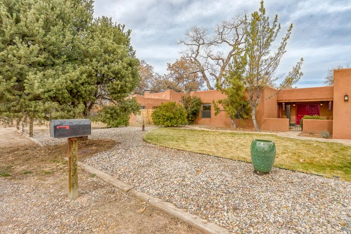 Beautiful adobe-style home with open, light, welcoming and flexible floor plan, backing up to the river with views of the bosque, all within the migratory bird flyway and hot air balloon box. 5 bedrooms, 3 baths & multiple living areas laid out to accommodate various configurations, including two Master suites, in-law wing and a detached casita/art studio space. Country living, with city shopping, dining, entertainment, farmers markets, Villages of Los Ranchos and Corrales all less than 10 minutes by car, bicycle or pedestrian/equestrian trails. Quiet, upscale, secluded, horse-friendly location, this home is nestled in the back of the neighborhood with gated access to the bosque and bridle trails. Heavily treed, landscaped one+acre lot with many fruit trees, grapes & mature cottonwood