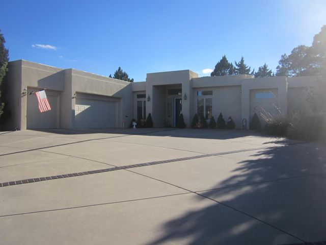 Gorgeous custom contemporary in Siesta Hills.   So close to KAFB, VA Hosp, Sunport,  Nob Hill & UNM.  Open plan with huge great room.  Gourmet kitchen with built in sub-zero refrig, bkfst bar, & tons of quality cabinets.  Semi-formal dining area + bkfst room.  Huge butler's pantry area.   Soaring ceilings & abundant windows bring in the natural light.  Just too many custom features &  extras to list.   BR next to MBR ideal for office or nursery.  Guest BR with in-suite bath ideal for in-law or teen.    Impressive circle drive leads to oversize 3 car finished  garage with laundry sink & storage galore.  Two HW heaters with quick hot water.   Big .38 acre lot with low maint landscaping.  Mature evergreens,  fruit trees, roses & privacy.   RV access possible on east side of house.   Sweet!