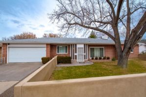 Charming single story brick home in the Albuquerque Country Club neighborhood with attached 2 car garage!  This mid century modern home has been remodeled throughout with solid hardwood floors, brand new kitchen with custom cabinets, quartzite countertops, and stainless steel appliances.  Refrigerated air and forced air both new in 2016.  A wood burning fireplace is the focal point for the main living area the 2nd living area has a cast iron gas stove to keep you warm.  Tastefully updated bathrooms.  Main bathroom has radiant heat and carrera marble countertop. Lush, mature landscaping with 6 zone irrigation system.  Enjoy all the outdoors have to offer from the covered gazebo.  Roof new in 2013/2018, electrical panel & lighting 2016-18, windows 2015, garage door 2014